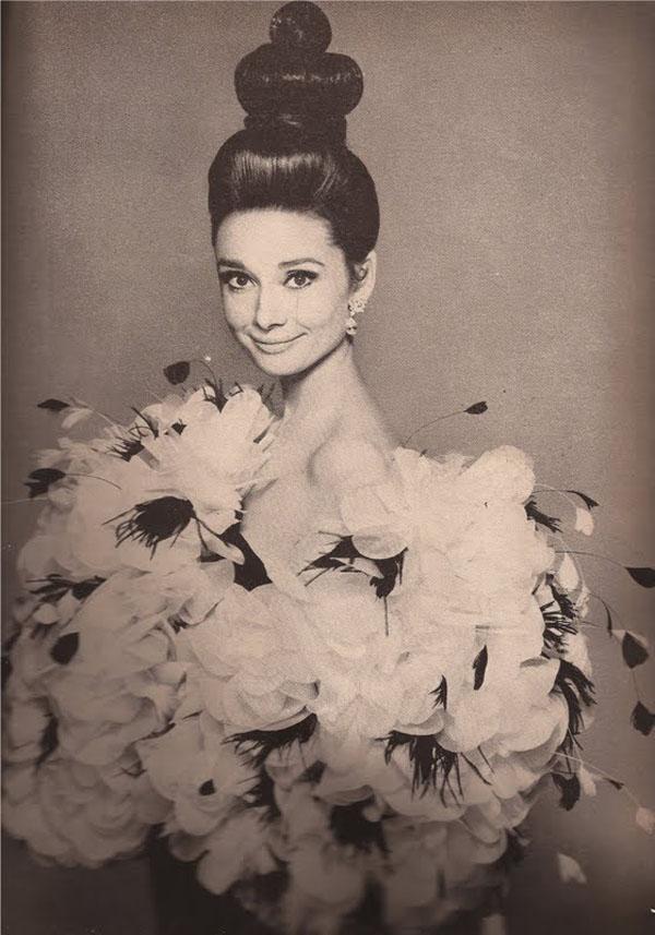 """Audrey Hepburn nel famoso scatto """"L'Abbraccio"""", avvolta da un soffio di petali d'organza e fiori di piume nella notte Parisienne di YSL."""