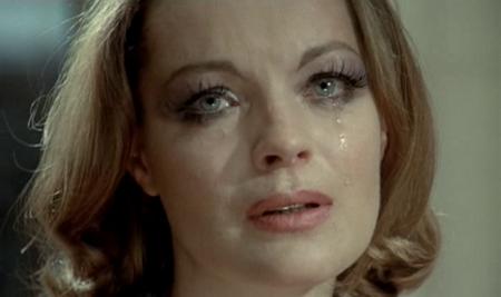 Romy Schneider si sbarazza delle forcine che sorreggono l'ingombrante acconciatura da Principessa Sissi per infilarsi nel négligé di Nadine Chevalier, attricetta del cinema osé ne L'importante è Amare (1975)