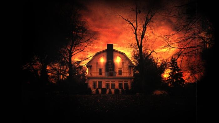 """Amityville Horror, il film maledetto per eccellenza, spegne 35 candeline insanguinate. Girato da Stuart Rosenberg nel 1979, la pellicola (ha avuto sette sequel, una parodia e un remake nel 2005) deve la sua (in)fam(i)a agli eventi narrati, realmente, accaduti nell'atroce notte del 12 novembre 1974 al 112 Ocean Avenue di Amityville, a Long Island New York, quando, la casa in stile colonia olandese risalente agli anni '20 fu teatro di una strage. Proprio tra quelle pareti, il ventitreenne Ronald DeFeo Jr. massacrò a colpi di fucile la sua famiglia: padre, madre e i quattro fratelli piccoli, senza apparente motivo. Condannato a venticinque anni e attualmente recluso nel carcere di Green Haven Correctional Facility a Beekman NY, il ragazzo ammise di averli uccisi spinto da alcune voci che gli aleggiavano in testa. L'anno seguente, i coniugi Lutz acquistarono Amityville e dopo appena 28 giorni ne fuggirono a gambe levate (con i tre figli di lei) asserendo che la dimora era funestata da macabri fenomeni paranormali. Sono proprio loro a raccontare la storia da brivido allo scrittore Jay Anson, che ne farà un bestseller nel '77. Si dice che durante la stesura del libro Frances Evans, un'amica dello scrittore, morì arsa in un incendio poco dopo aver ricevuto i primi capitoli da leggere. Oggi, celebriamo il raccapricciante 35th anniversario dell'opera cinematografica (uscì il 27 luglio di 35 anni fa) tratta dall'omonimo romanzo con Le Terrificanti Dimore Infestate dello Schermo: dalla villetta in stile coloniale di Ocean Avenue alla Murder House di American Horror Story, passando per la """"preistorique"""" Maison Ensorcelée fino alla più recente Harrisville in The Conjuring."""