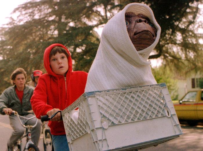 Il piccolo Elliott (Henry Thomas) e l'alieno E.T. scappano in sella alla bici dalle grinfie della NASA nella favola sci-fi di Steven Spielberg (1982)