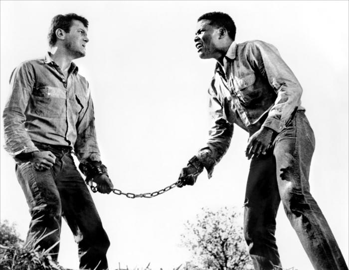 Il razzista Tony Curtis e l'afro Sidney Poitier sono detenuti in fuga, incatenati l'uno all'altro, ne La Parete di Fango (1958)