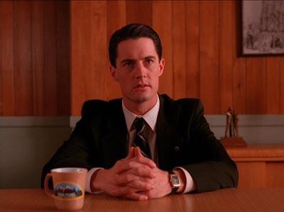 Il detective Cohle alla alla scrivania con lo sguardo rivolto a sinistra e la tazza di caffè beige nel lato opposto.