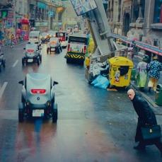 """Le piccole auto """"futuristiche"""" che sfrecciano sull'asfalto attraversato da Qohen Leth sono le vetture elettriche, Renault Twizy."""