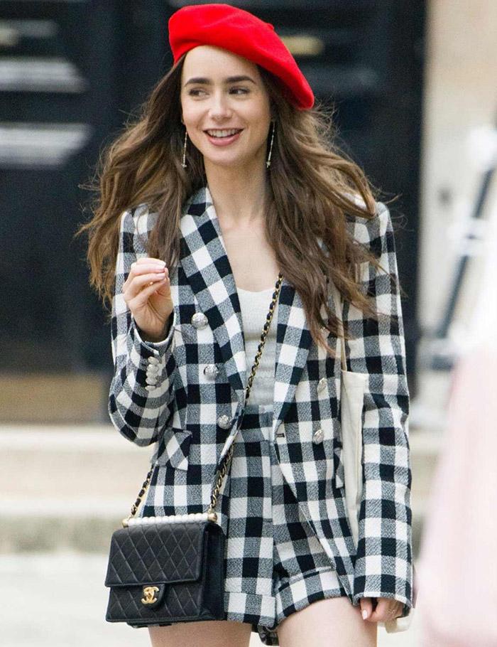 In Veronica Beard (blazer a quadri), Galeries Lafayette (basco rosso) e iconica borsa Chanel